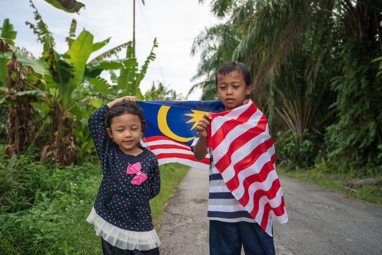 Siblings Holding Malaysian Flag While Standing On Road Amidst Plants