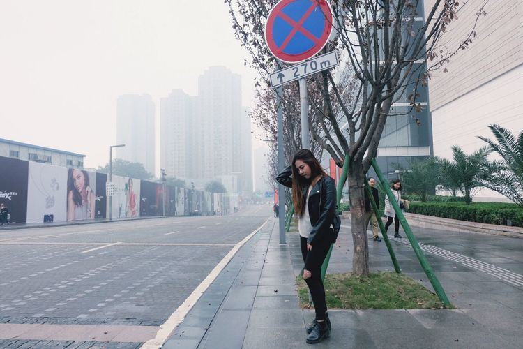 Full length of woman standing on road in city