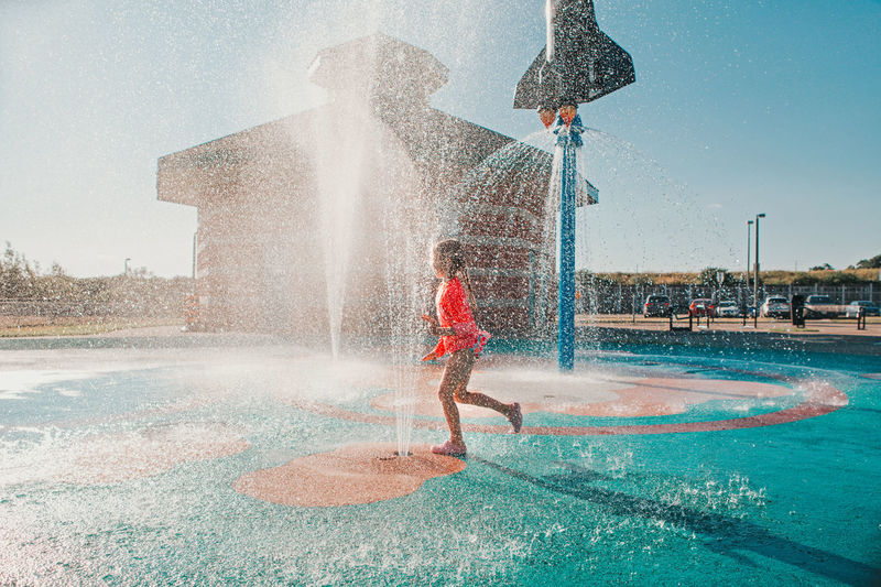 Funny girl playing on splash pad playground on summer day. happy child having fun in water.
