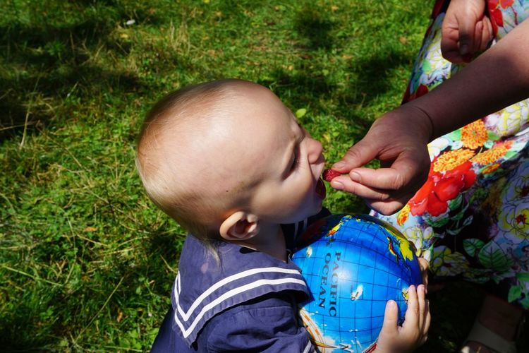 Cropped hand of mother feeding baby boy standing at back yard
