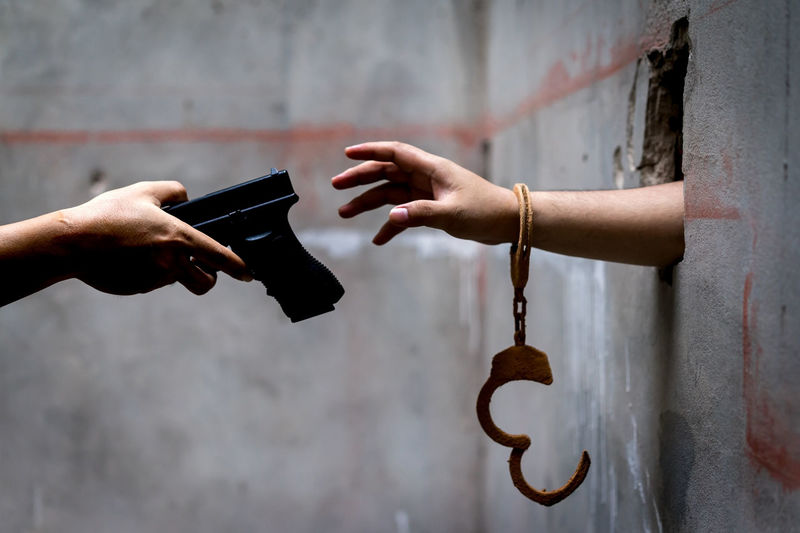 Man prisoners with shackle are trapped in the dungeons is asking for help, but with a hand gun, the men are filed. Crime Gun Hands Jail Man Prisoner Security Behind Black Criminal Criminals Depression Despair Handcuff Handgun Justice Killer Law Lock Pistol Prison Sad Shackle Violence Weapon