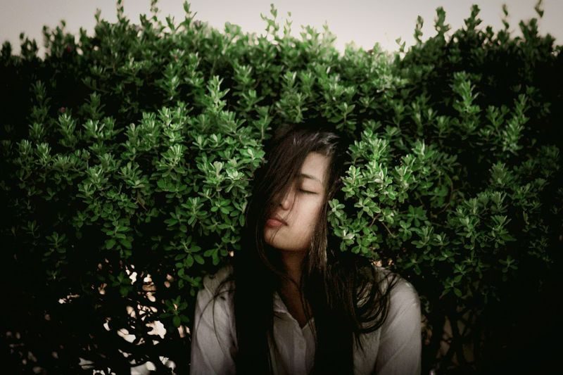 Young woman with eyes closed sitting amidst plants