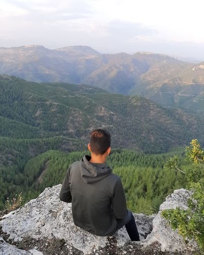 High angle view of boy sitting on cliff against mountains