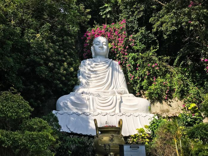 Statue of white flowers against trees
