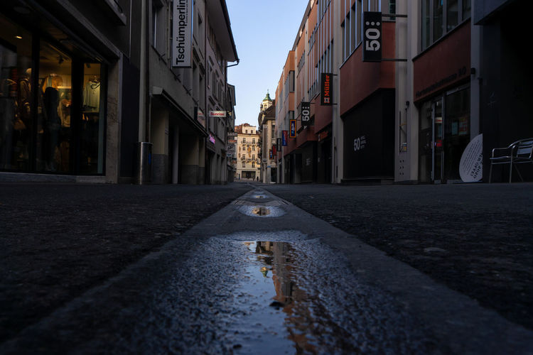 Surface level of wet street amidst buildings in city