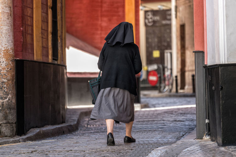Rear view of nun walking on city street