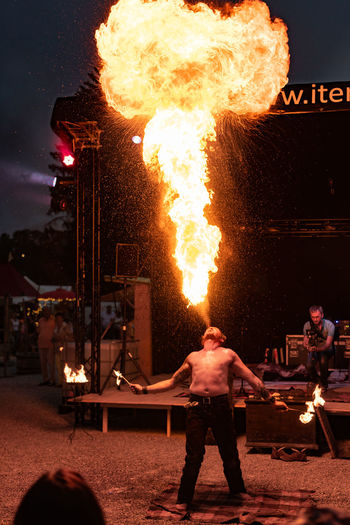 Burning Fire Flame Night Fire - Natural Phenomenon Heat - Temperature One Person Standing Performance Real People Communication Nature Warning Sign Sign Illuminated Skill  Glowing Men Motion Outdoors Entertainment Event