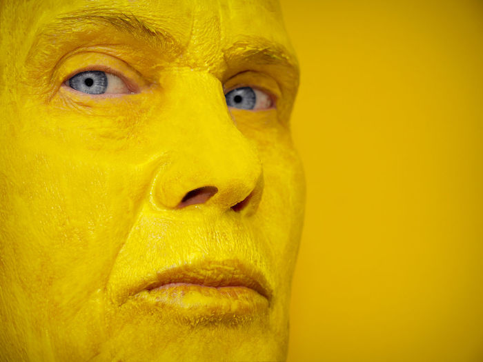 Close-Up Portrait Of Woman With Face Paint Against Yellow Background