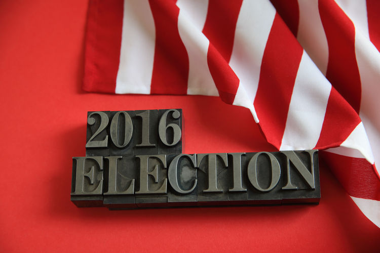 American flag on red with 2016 election words 2016 Elections American Flag Close-up Country Government Indoors  Letters Metal Type Nation Natural Light No People Numbers Political Politics Presidential Election Red Stripes Pattern Symbol Text Type Typography USA Voting White Words