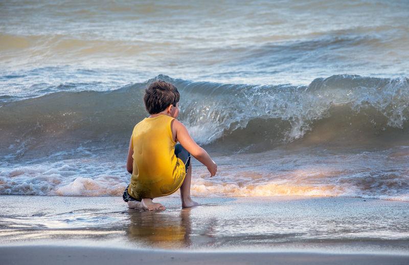 Rear view of boy on beach