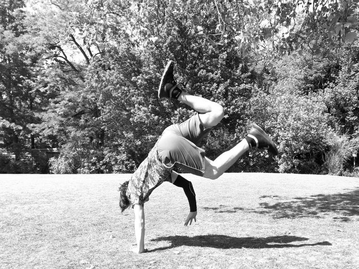 Side view of woman jumping against trees