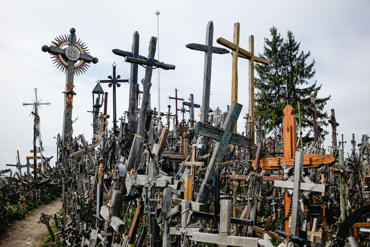 Low angle view of cross amidst trees against sky