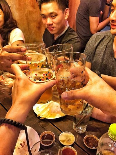 Close-up of friends drinking glass on table