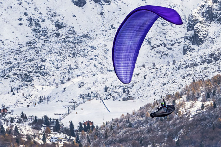 High angle view of person paragliding over snowcapped mountain