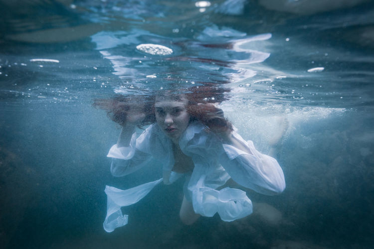 Portrait of young woman swimming underwater in sea