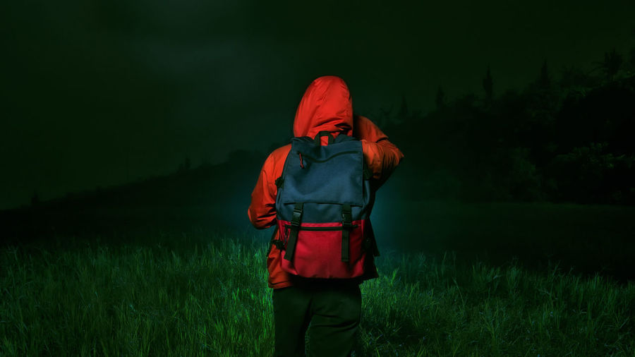 Rear View Of Woman Walking On Field At Night