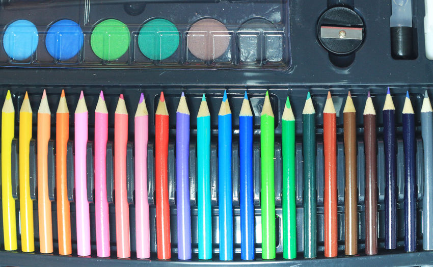 Close-up of multi colored pencils in row