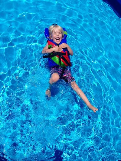 Portrait of happy boy playing in swimming pool
