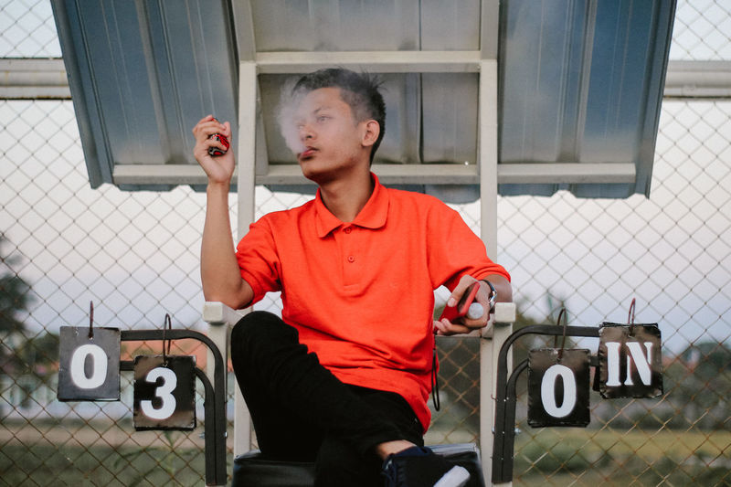 Young man smoking electronic cigarette while sitting on tennis court