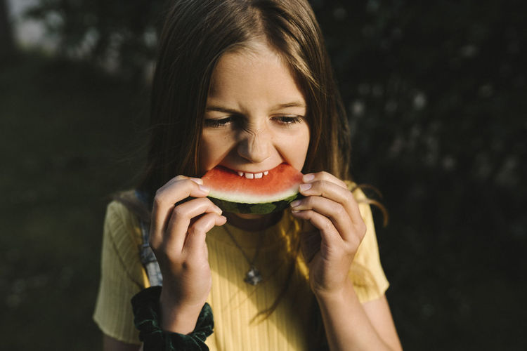 Portrait of young woman eating fruit