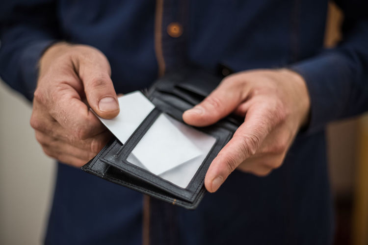 Midsection of man holding placard in wallet