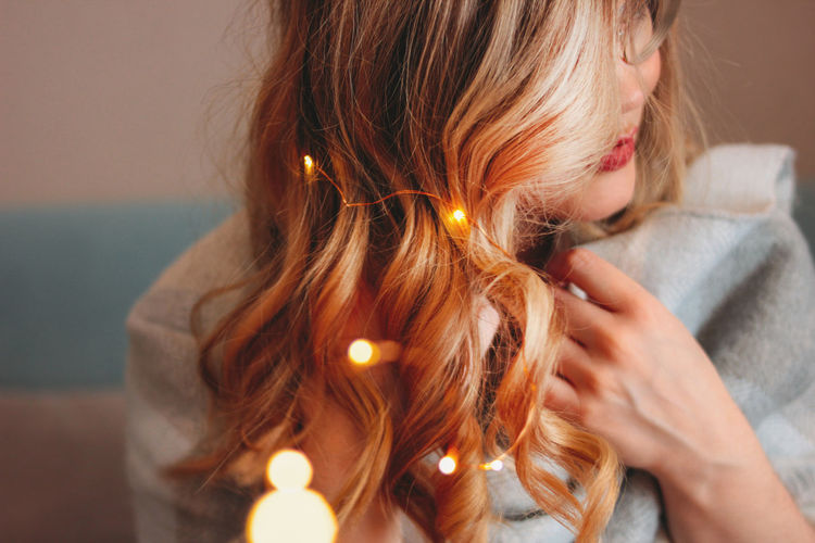 Young charming blonde woman in glasses with lights in her hair, romantic atmospheric photo about dreams, blurred focus One Person Headshot Women Adult Holding Hair Illuminated Close-up Portrait Focus On Foreground Hairstyle Indoors  Child Females Girls Brown Hair Candle Burning Contemplation