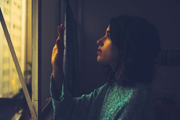 Side view of young woman looking through window