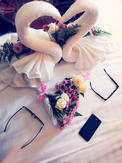 High angle view of towels and bouquets decorated on bed