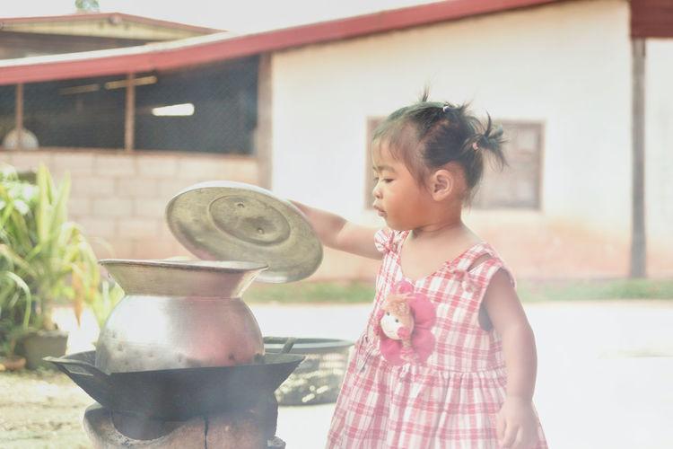 Baby girl opening utensil on wood burning stove at backyard