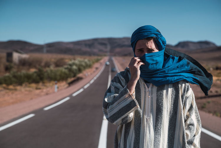 Portrait of man standing on road against blue sky