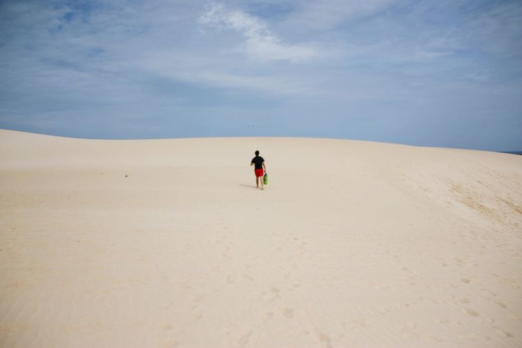 Rear view of person walking on sand dune at fuerteventura against sky