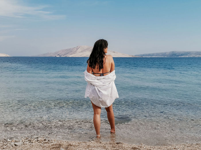Rear view lifestyle image of stylish young woman in white shirt standing on beach and looking at sea