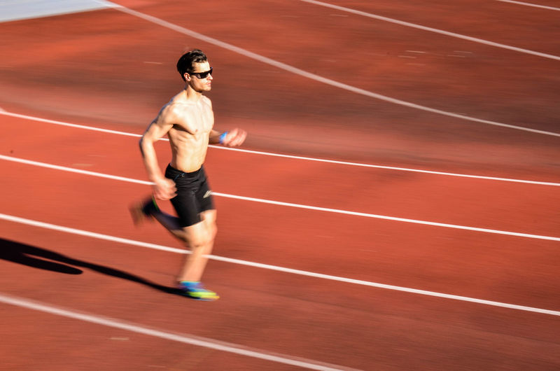 Blurred motion of shirtless man running on track