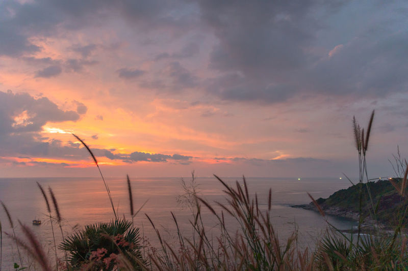 panorama sunset at Laem Promthep Cape. The landmark and popular viewpoint of Phuket Thailand. in every day a lot of tourists come here to watching sunset. Promthep Cape,phuket,landmark,travel, Promthep Phuket Landmark Viewpoint Famous Place Sunset, Sky Cloud - Sky Sweet Water Beauty In Nature Sunset Scenics - Nature Tranquility Tranquil Scene Sea Plant Nature No People Beach Horizon Land Growth Horizon Over Water Non-urban Scene Idyllic Outdoors Marram Grass Timothy Grass