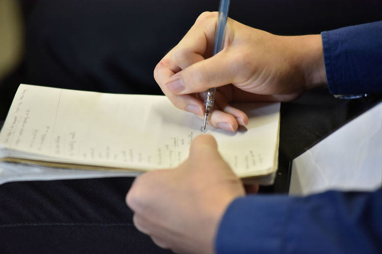 Midsection of man writing in diary while sitting at office