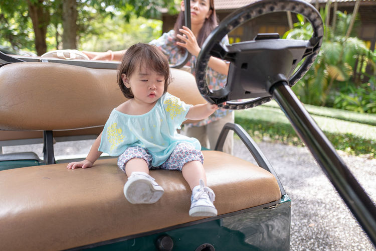 Woman Standing By Daughter Sitting On Golf Cart