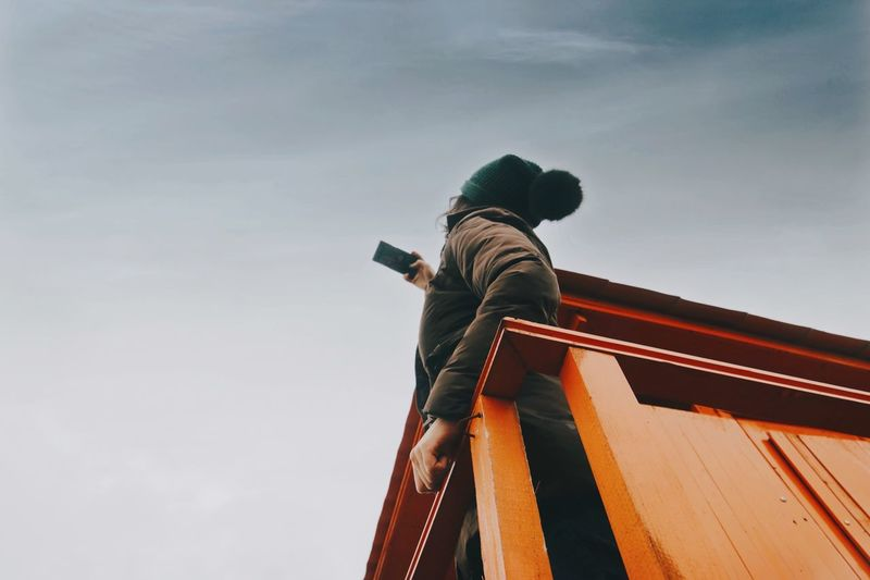 Woman taking selfie while standing at lookout tower against sky