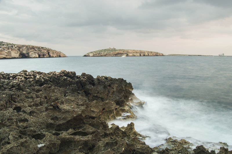 Scenic view of sea and rocks against cloudy sky