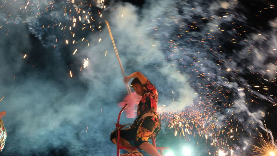 Low angle view of woman with fire crackers at night