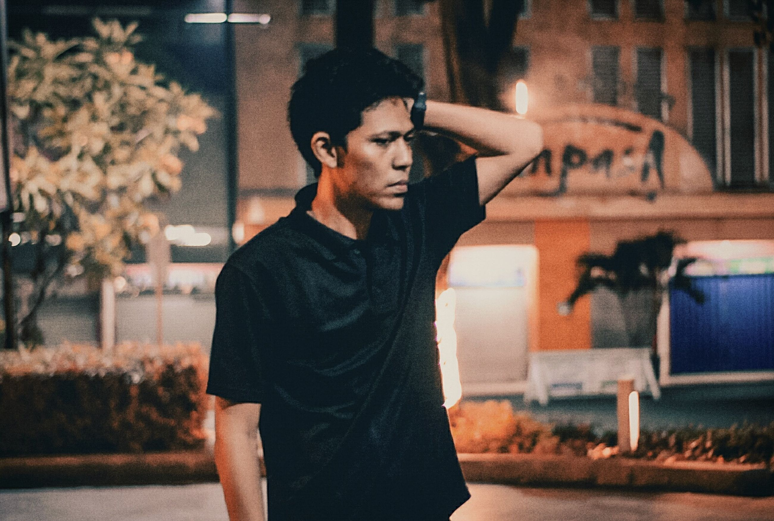 one person, young adult, focus on foreground, standing, real people, leisure activity, lifestyles, young men, portrait, front view, waist up, looking at camera, casual clothing, contemplation, three quarter length, looking, architecture, outdoors, waiting, hairstyle