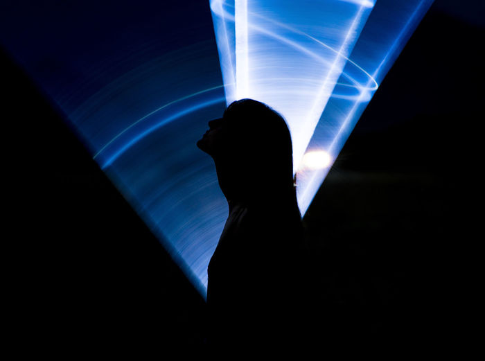 Silhouette person with illuminated light painting at night