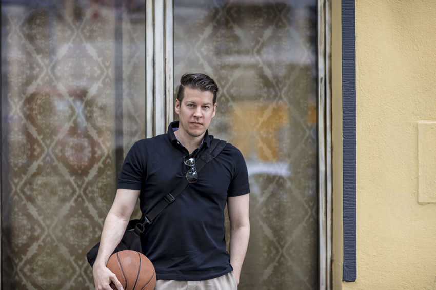 Man wearing khaki pants and a golf shirt holding a basketball in his hand posing for the camera in front of window. Medium shot. Adult Basketball Khaki Pants Man Sunny Afteroon Casual Clothing Caucasian Causal Clothing Curtains Day Golf Shirt Good Looking Hand In Pocket Handsome Male Medium Shot Model Outdoors Outside Portrait Posing Summer Urban Window