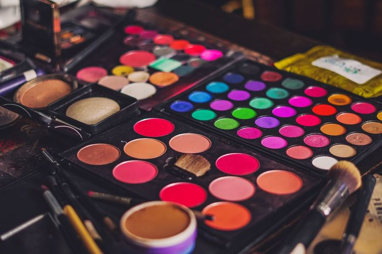 Close-up of multi colored makeup box on table