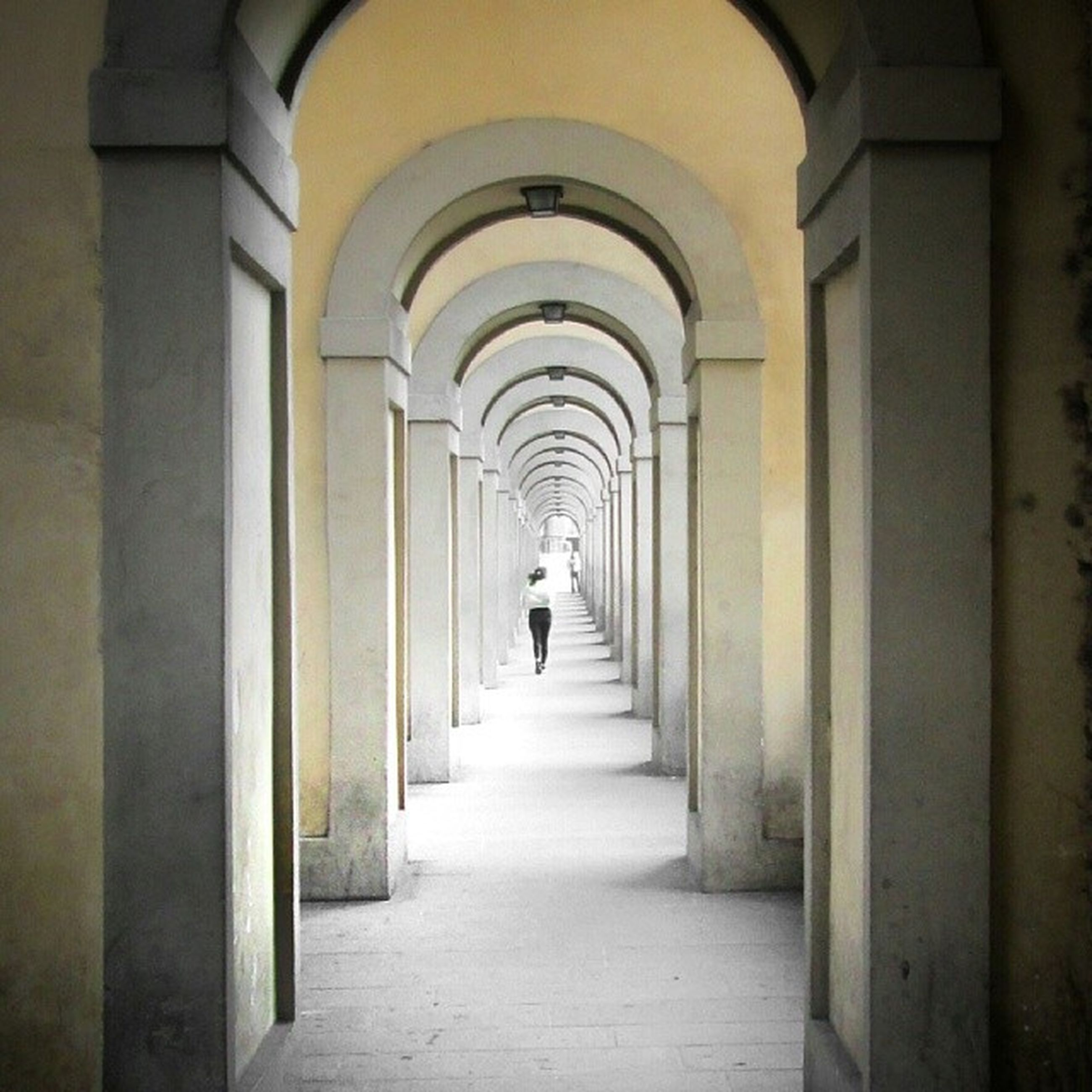 indoors, the way forward, full length, arch, walking, rear view, corridor, architecture, lifestyles, men, built structure, tunnel, person, diminishing perspective, leisure activity, archway, architectural column, vanishing point