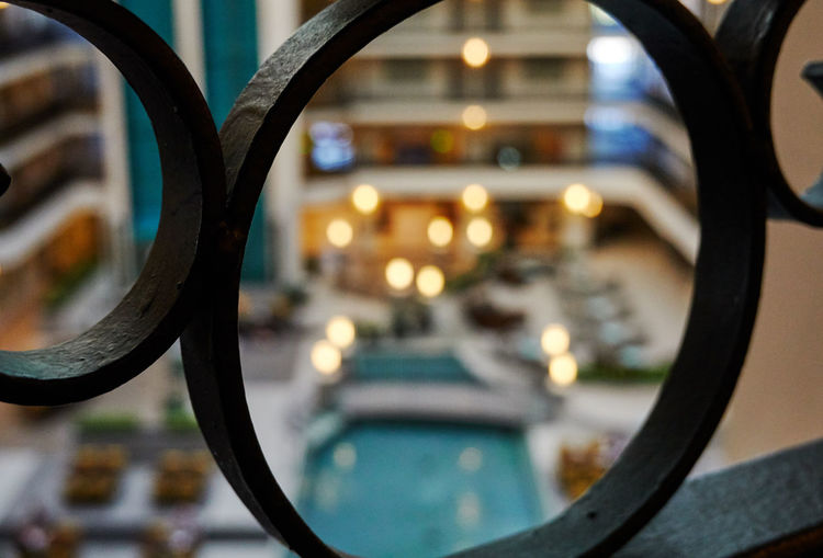 Close-up of metal railing by swimming pool in city