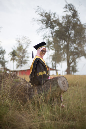 Portrait Of Woman In Graduation Gown Sitting On Log