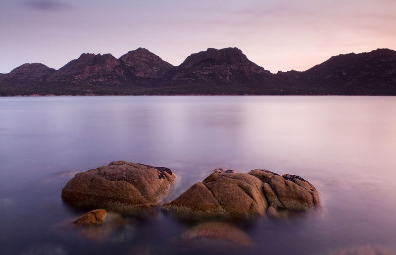 Scenic view of rocks in lake against sky during sunset