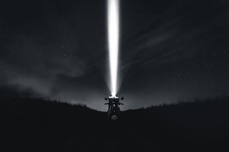 Silhouette man with illuminated flashlight against sky at night