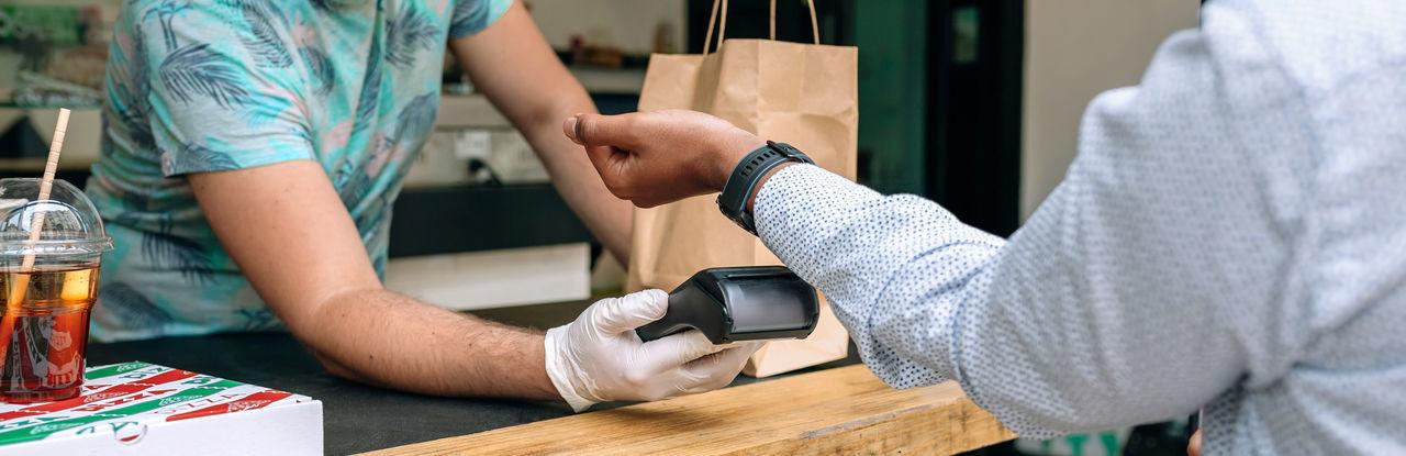 Man making contactless payment through smart watch at restaurant