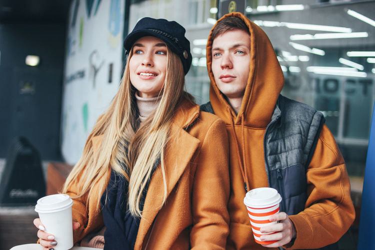 Young couple holding coffee sitting in cafe